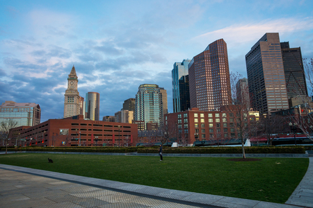 Boston, USA - April 27, 2015: Financial District and Custom House Tower at North End Park at Cross Street in downtown Boston, Massachusetts, the United States. People on background
