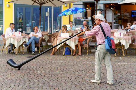 entertain: Ascona, Switzerland - August 23, 2016: Alphorn player entertain people at the restaurant of Ascona on Lake Maggiore, Ticino canton, Switzerland.
