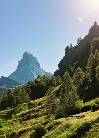 Matterhorn mountain and green hill in Zermatt, Switzerland in summer. With special sun flare Stock Photo