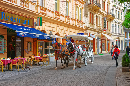 the coachman: Karlovy Vary, Czech republic - May 5, 2014: Horse carriage at Promenade street, Karlovy Vary, Czech republic. People on the background Editorial