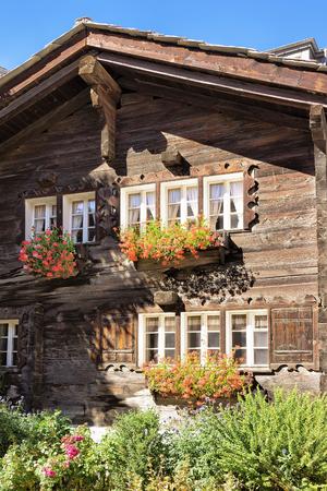 Traditional Swiss chalet with flowers on balconies in Zermatt resort village of Switzerland in summer