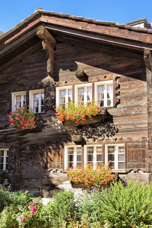 Traditional Swiss chalet with flowers on balconies in Zermatt resort village of Switzerland in summer