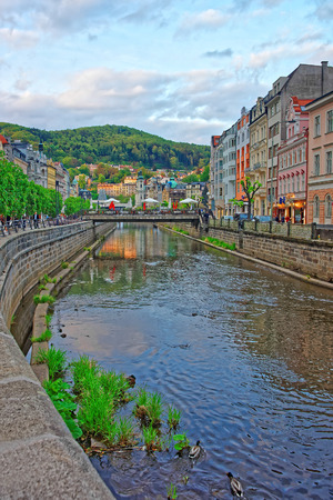 Karlovy vary, Czech republic - May 5, 2014: Tepla River embankment and St Mary Magdalene Church in Karlovy Vary, Czech republic. People on the background.