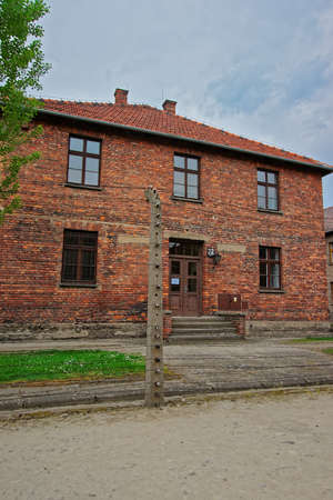 jewish community: Auschwitz, Poland - May 2, 2014: Razor wire and barracks in Auschwitz concentration camp, Poland.