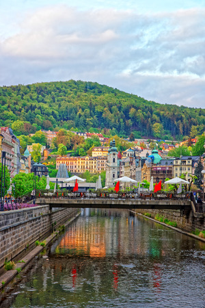 Karlovy vary, Czech republic - May 5, 2014: Tepla River embankment and St Mary Magdalene Church of Karlovy Vary, Czech republic. People on the background.