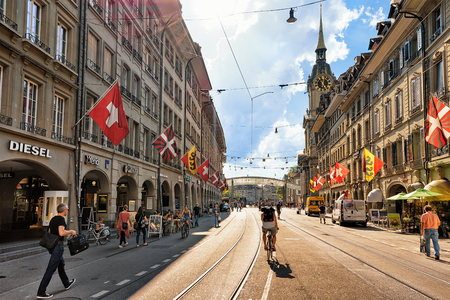 Bern, Switzerland - August 31, 2016: People on Spitalgasse street with shopping area in old city center of Bern, Switzerland. Steeple of Holy Spirit Church on the background