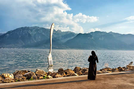 purdah: Vevey, Switzerland - August 27, 2016: Muslim woman in black burqa at Fork sculpture at Geneva Lake of Vevey Riviera, Vaud canton, Switzerland. Alps mountains on the background Editorial