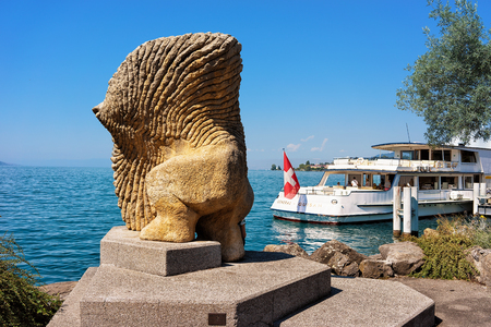 montreux: Montreux, Switzerland - August 27, 2016: Statue and Excursion ferry with people aboard at Geneva Lake in Montreux, Vaud canton, Switzerland Editorial