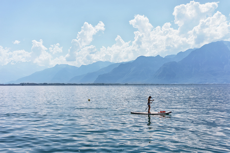 montreux: Montreux, Switzerland - August 27, 2016: Girl standing on standup paddle surfing in Geneva Lake in Montreux of Switzerland Editorial