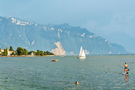Vevey, Switzerland - August 27, 2016: Ship and people at Geneva Lake in Vevey, Vaud canton, Switzerland. Alps mountains on the background