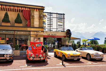 entertainment center: Montreux, Switzerland - August 27, 2016: Retro cars parked near Casino building at Geneva Lake in Montreux, Vaud canton, Switzerland. People on the background