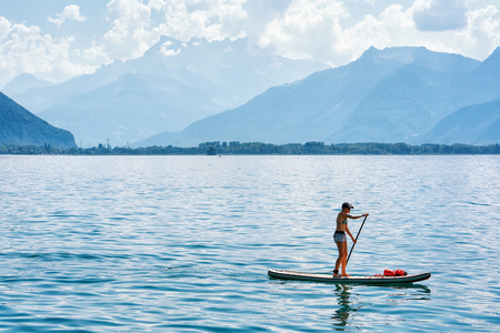 Montreux, Switzerland - August 27, 2016: Girl standing on standup paddle surfing on Geneva Lake in Montreux, Vaud canton, Switzerland Editorial