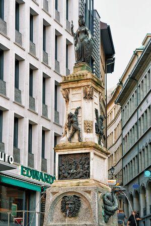 cite: Geneva, Switzerland - August 30, 2016: Fountain at Rue de la Cite in Geneva city center, Switzerland.