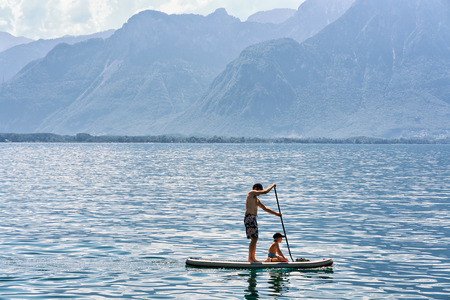Montreux, Switzerland - August 27, 2016: Man and boy on Standup paddle surfing board on Geneva Lake in Montreux, Vaud canton, Switzerland