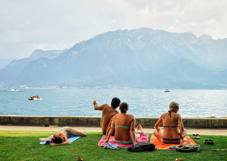 Vevey, Switzerland - August 27, 2016: People sunbathing at the embankment of Geneva Lake in Vevey, Vaud canton, Switzerland