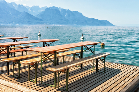 montreux: Wooden tables with chairs for relaxation at Geneva Lake in Montreux, Vaud canton, Switzerland