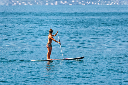 Girl standing on standup paddle surfing in Geneva Lake in Montreux, Switzerland