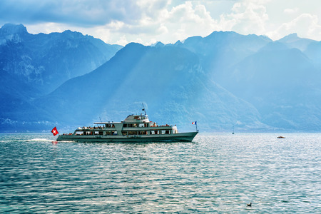 Excursion ferry at Geneva Lake in Vevey, Vaud canton of Switzerland. Alps mountains and people on the background