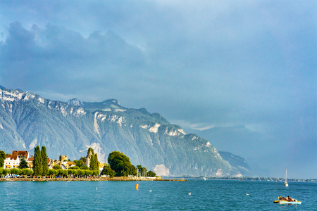 Scenery with Alps mountains and Geneva Lake Riviera at Vevey, Vaud canton, Switzerland. People on the background Stock Photo