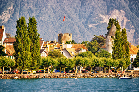 Town with towers and Alps mountains, and Geneva Lake Riviera in Vevey, Vaud canton, Switzerland. People on the background
