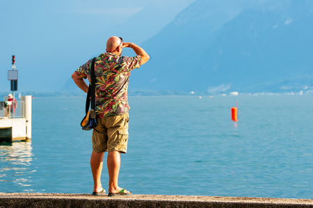 Man looking into distance at the embankment on Geneva Lake in Vevey, Vaud canton, Switzerland