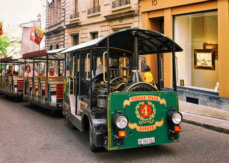 Geneva, Switzerland - August 30, 2016: People in excursion tram at Street with Flags on Rue de Hotel-de-Ville in Geneva old town, Switzerland Editorial