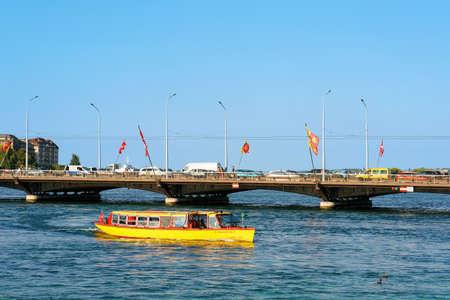 Geneva, Switzerland - August 30, 2016: Excursion ferry in Geneva Lake and Pont des Bergues bridge with flags in Geneva city of Switzerland. People on the background