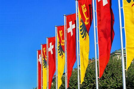 Swiss flags and Geneva canton flags on promenade of Lake Geneva of Switzerland