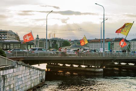 Geneva, Switzerland - August 30, 2016: Geneva Lake and Mont-Blanc bridge with many Swiss flags, Geneva, Switzerland. People on the background Editorial