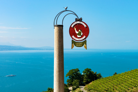 Lavaux, Switzerland - August 30, 2016: Round name sign at Vineyard Terraces hiking trail of Lavaux, Lake Geneva and Swiss mountains, Lavaux-Oron district in Switzerland. Bird sitting on the plate