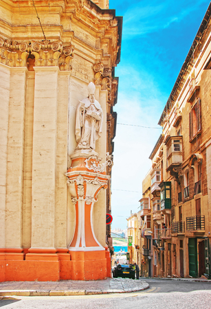 Figure of a Saint at the corner of Church of St Augustine in Valletta old town, Malta Stock Photo
