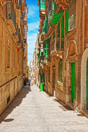 Valletta, Malta - April 3, 2014: Houses with green balconies of Valletta old town, Malta. People on the background