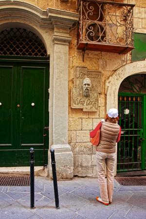 Valletta, Malta - April 3, 2014: Woman tourist looking at the Van Gogh stone head in the street of Valletta old town, Malta Editorial