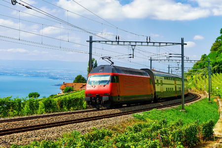 Running train and the railroad in Lavaux Vineyard Terraces hiking trail at Lake Geneva and Swiss mountains, Lavaux-Oron district, Switzerland Stock Photo