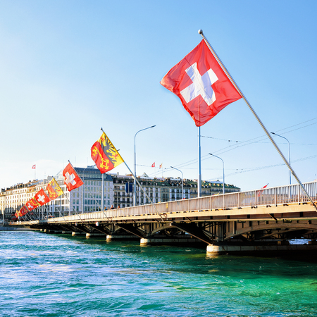 central european: Geneva Lake and Mont-Blanc bridge with many flags, Geneva, Switzerland. People on the background Stock Photo