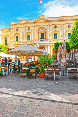 Valletta, Malta - April 3, 2014: People resting at open air cafes on Republic Square with National Library in Valletta old town, Malta