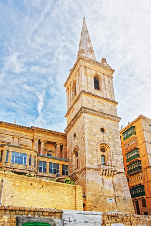 Street view of spire of Saint Paul Cathedral in Valletta old town, Malta