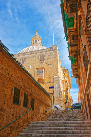 Street with staircase and dome of Carmelite Church at Valletta old town, Malta