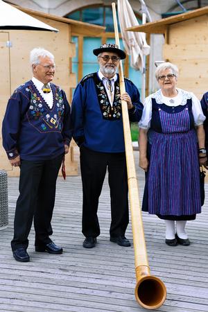 alphorn: Zermatt, Switzerland - August 24, 2016: Alphorn player with senior people in traditional Swiss costumes