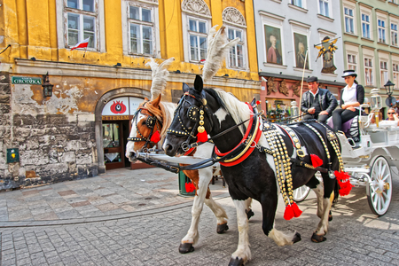 Krakow, Poland - May 1, 2014: Horse fiacre and people at the Old town in Krakow, Poland