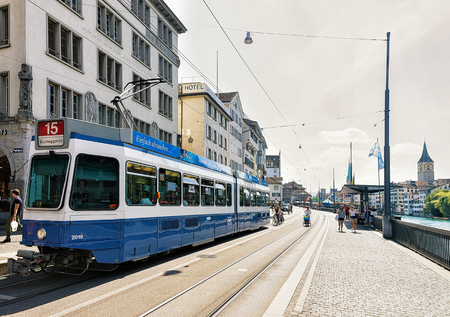 Zurich, Switzerland - September 2, 2016: Running Tram at Limmatquai and Saint Peter Church and Fraumunster Church in the city center of Zurich, in Switzerland. People on the background