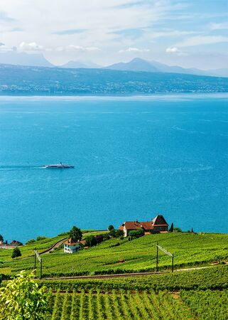 Railway line at Lavaux Vineyard Terraces hiking trail, Lake Geneva and Swiss mountains, in Lavaux-Oron district, in Switzerland. Ship on the background