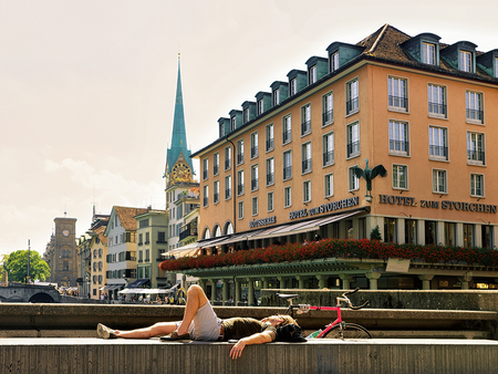 Zurich, Switzerland - September 2, 2016: Man relaxing at Limmatquai and Fraumunster Church in the city center of Zurich, in Switzerland.