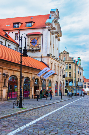 poznan: Poznan, Poland - May 7, 2014: Cobblestone Paderewski street in the Old Town of Poznan, Poland. People on the background.