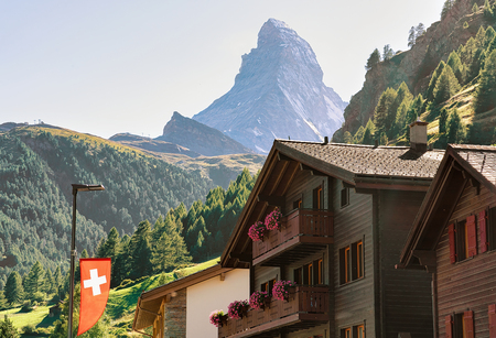 Traditional Chalets in Zermatt with Matterhorn peak with Swiss flag, Switzerland in summer. Standard-Bild