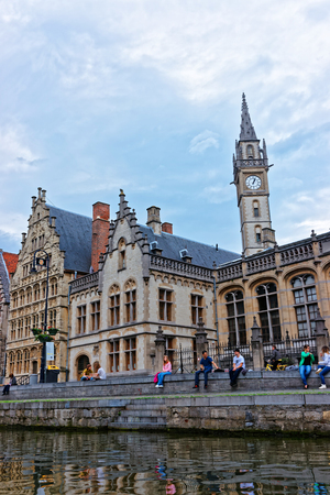 Ghent, Belgium - May 10, 2012: Guildhalls and Clock tower of Former Post Office Pavilion in Graslei in Ghent in East Flanders, Belgium. People at the Canal of Leie River