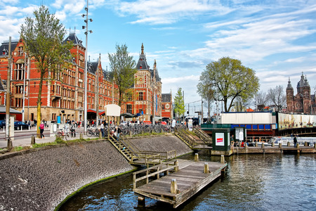 Amsterdam, Netherlands - May 3, 2013: Canal on Open Havenfront in Amsterdam, Netherlands. Centraal train station and people on the background
