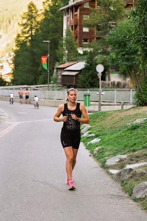 scamper: Zermatt, Switzerland - August 24, 2016: Young girl running at resort city in Switzerland in summer.