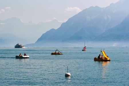 Lausanne, Switzerland - August 26, 2016: People in catamarans on Lake Geneva in Lausanne, Switzerland