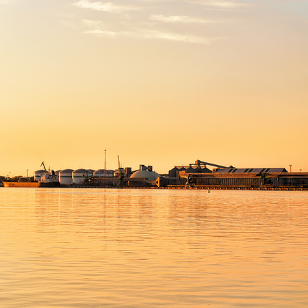 Oil tanks in Baltic sea in Port, Klaipeda, Lithuania. Magic golden light at sunset Stock Photo